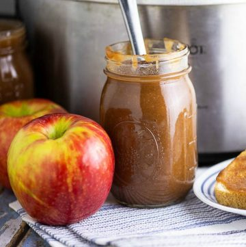A jar of apple butter next to honeycrisp apples in front of a stainless steel Crock Pot