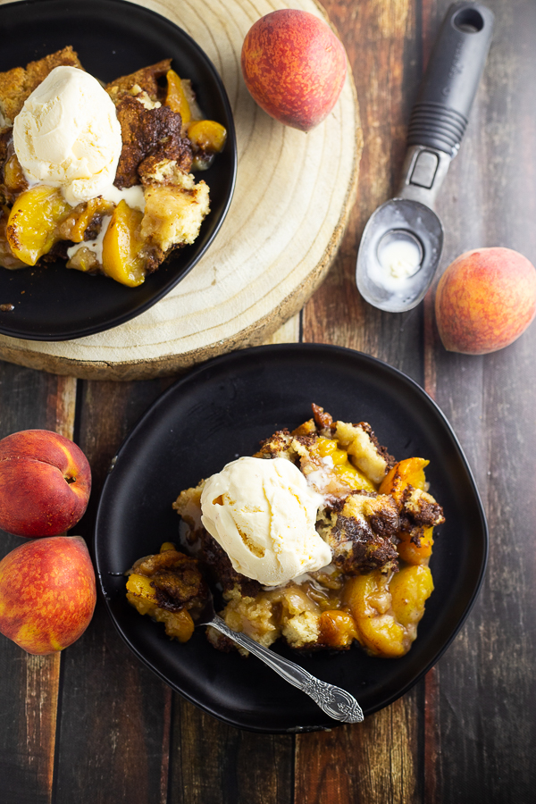 Overhead picture of peach cobbler topped with vanilla ice cream on a plate next to a spoon with another plate of peach cobbler next to it along with an ice cream scoop and 4 fresh peaches scattered around