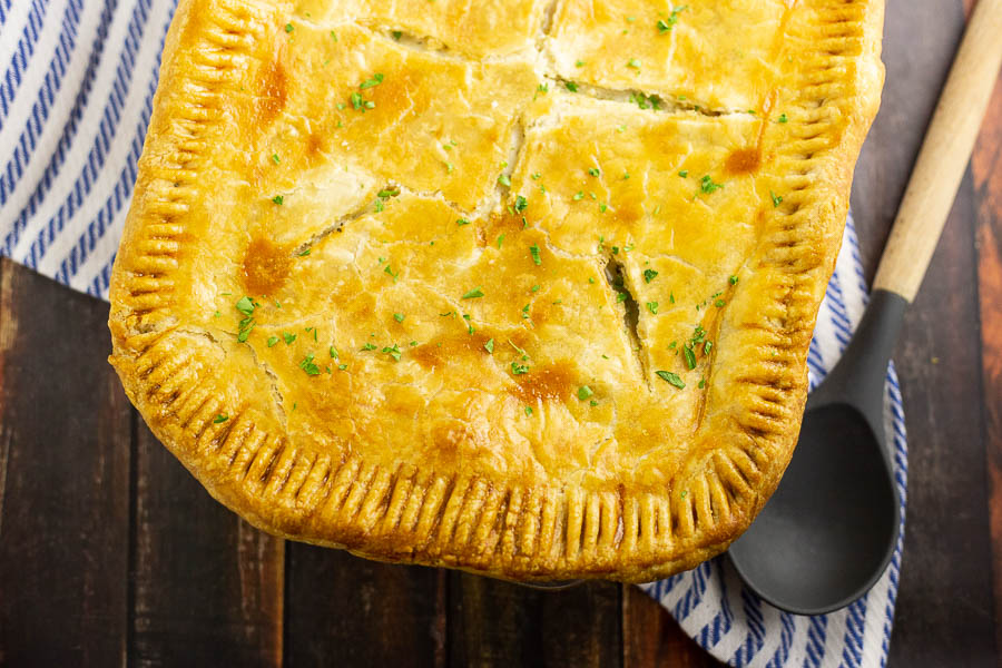 Fully baked golden chicken pot pie on a dark rustic wood background with a wooden spoon and striped cloth napkin.