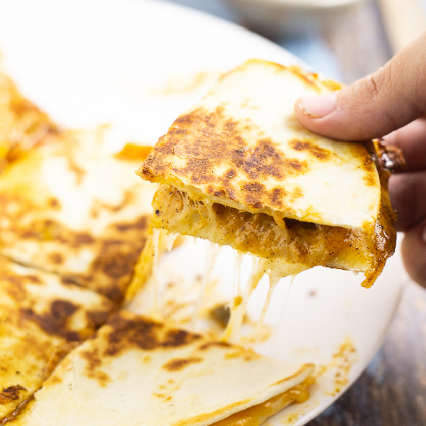 Hand picking up a quarter of a gooey, cheesy quesadilla from a white plate.