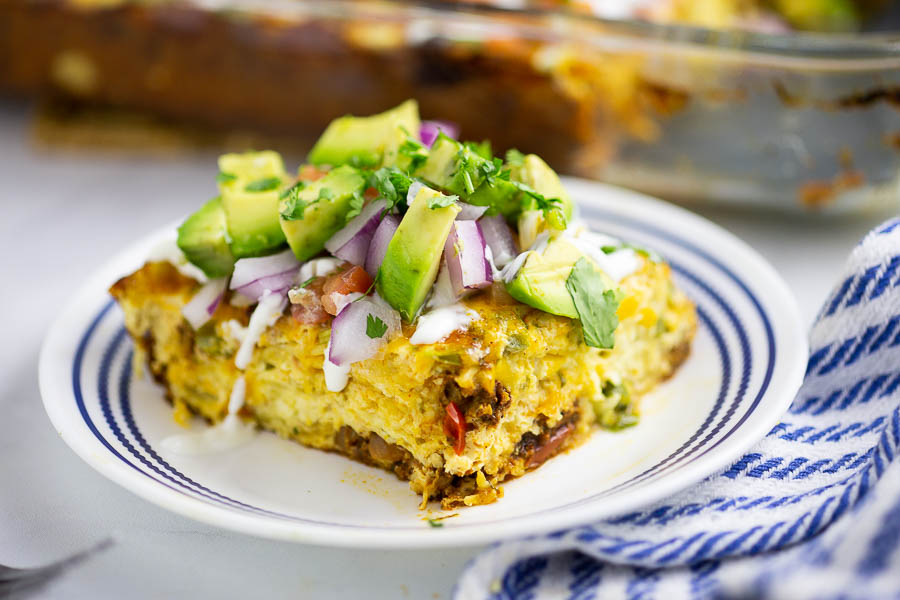 Mexican breakfast casserole on a small white and blue plate, topped with avocado next to blue and white linen and full casserole in the background.