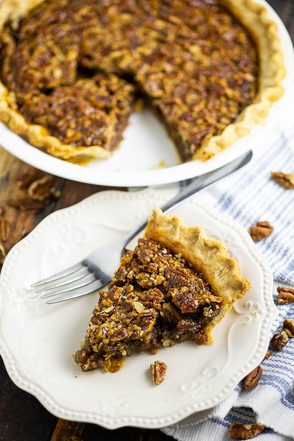 Slice of pecan pie on a cream colored plate with pecans scattered around on a blue and white striped linen.