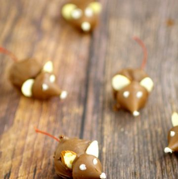 These fun Chocolate CherryChristmas Mice made from chocolate covered cherries with almond slices and Kisses, are adorable Christmas candy treats recipe and a great addition to your dessert table. These will be so cute next to all the Christmas cookies!