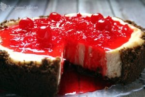 This Gingersnap Cherry Cheesecake has a gingersnap crumb crust, classic cheesecake filling, and a sweet cherry sauce topping.  From TheGraciousWife.com
