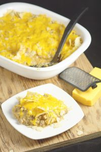 This Taco Bake Casserole recipe makes family taco night even more delicious with gooey cheese, crunchy tortilla chips, and perfectly seasoned taco meat. Quick and easy dinner recipe idea that the whole family will love! My husband used to eat this when he was a kid! So yummy!