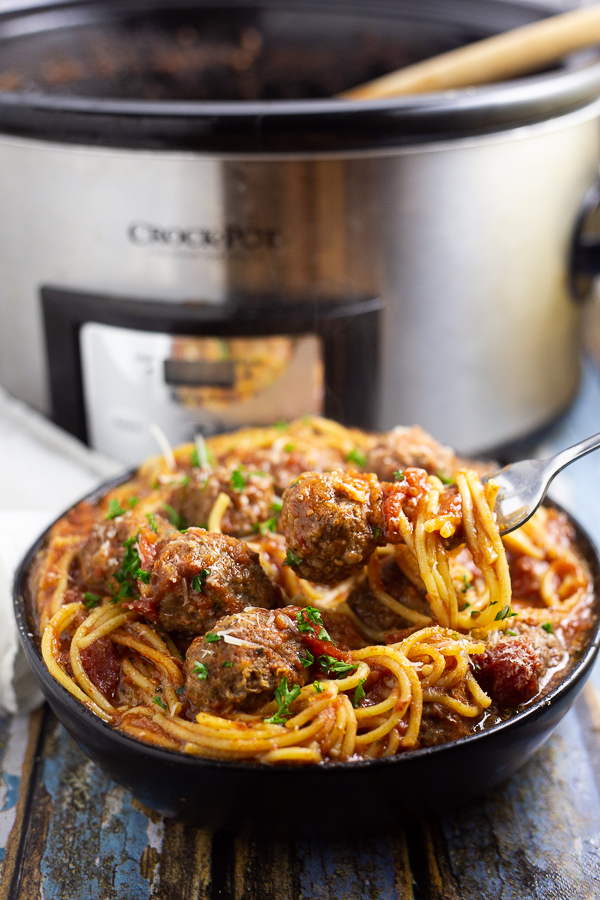 Crock Pot Spaghetti and Meatballs in a shallow bowl with a fork picking some spaghetti and a meatball with a slow cooker in the background
