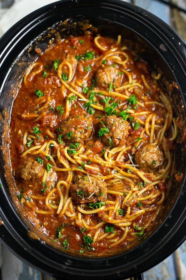 Crock Pot Spaghetti and Meatballs in a slow cooker with fresh parsley on top