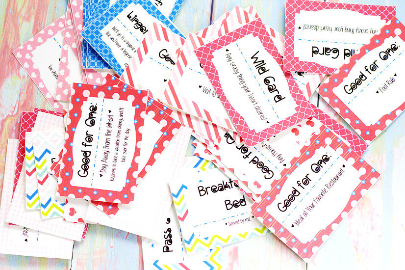 Cut out love coupons in a pile on a pastel rainbow wood background