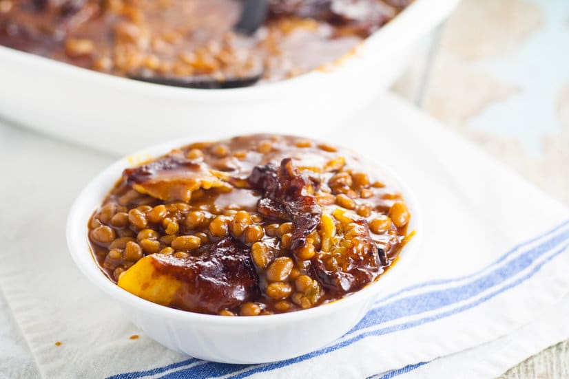 Homemade Bacon Baked Baked Beans are easier to make than you think! Sweet and tangy Homemade Bacon Baked Beans, slow baked with bacon are the perfect summer side dish for your next barbecue or cookout! Yum!