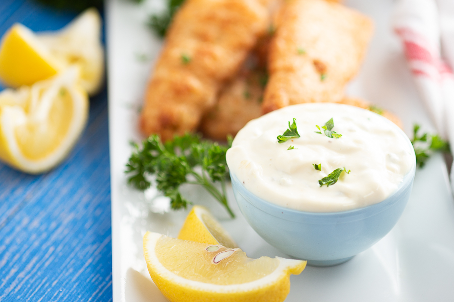 Homemade tartar sauce in a blue bowl with lemon wedges around