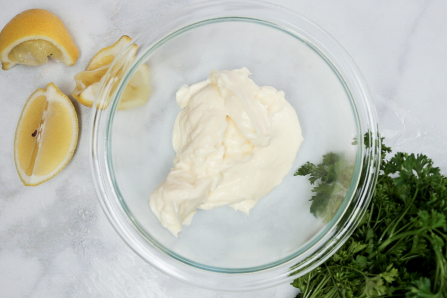 Mayo in clear bowl with lemons and parsley in background on white marble counter