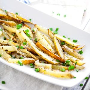 Garlic Chive Baked French Fries recipe - This Garlic Chive Baked French Fries recipe turns an American classic into a zesty new favorite with fresh garlic and chives tossed with butter and fries and baked in the oven. This looks like a fabulous quick and easy side dish recipe!  What's not to love?!