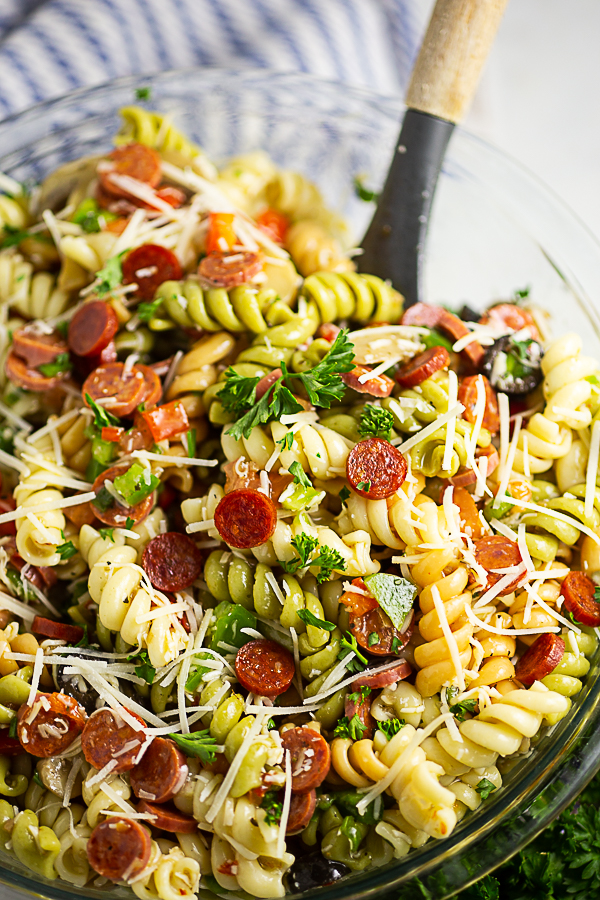 Close up of a glass bowl of pizza pasta salad topped with chopped parsley and grated parmesan with a wooden spoon in it.