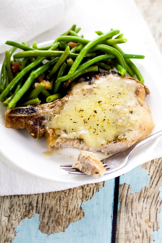 Cheesy Italian Pork Chops Recipe - Juicy, flavorful pork chops, baked in the oven with garlic and Italian seasoning and smothered in cheese in this Cheesy Italian Pork Chops recipe. Make it in just 40 minutes! These are seriously delicious!
