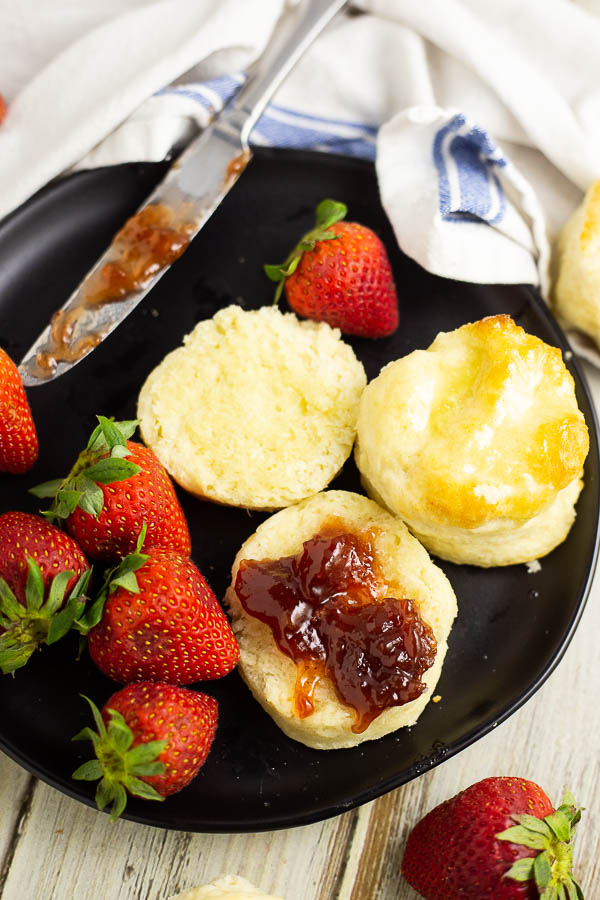 Two biscuits on a black plate plate with strawberries. One biscuit is cut open with strawberry jam spread on it
