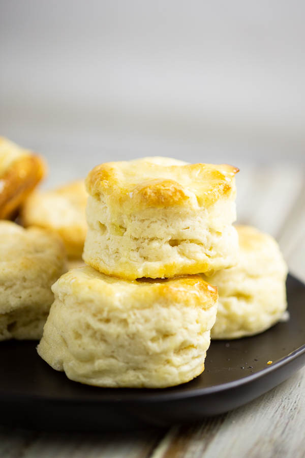 Biscuits stacked on a black matte plate on a white rustic wood background