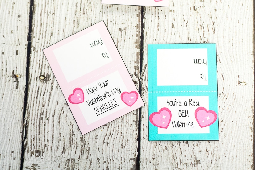 Pink and aqua Ring Pop Valentines on white wood background after being printed and cut out