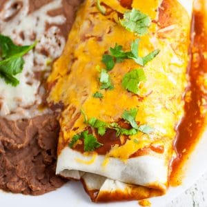 Rice and Black Bean Burritos Recipe - Quick and easy Mexican-inspired dinner recipe, these Rice and Black Bean Burritos are filled with flavorful rice and beans and smothered in enchilada sauce and cheese for a yummy vegetarian dinner perfect for Meatless Monday.