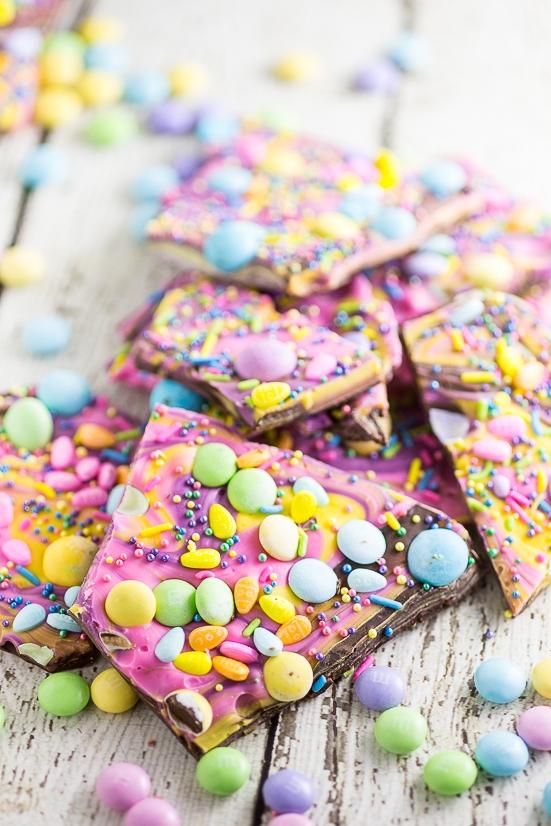 Pile of colorful swirled chocolate Easter bark with pastel Easter candies on a white wood background