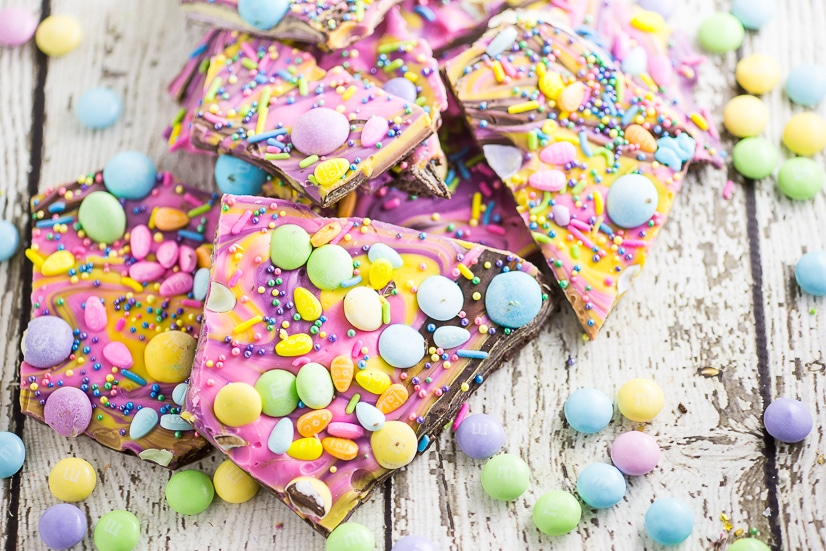 Chocolate Easter Bark with pastel Easter candies on a white wood background