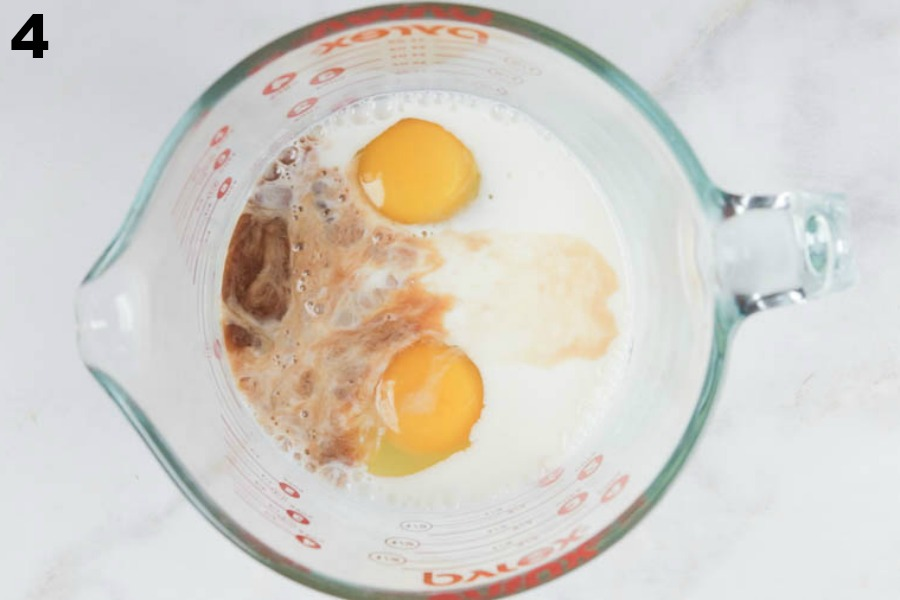 Wet ingredients, eggs, milk, and vanilla, in a glass measuring cup