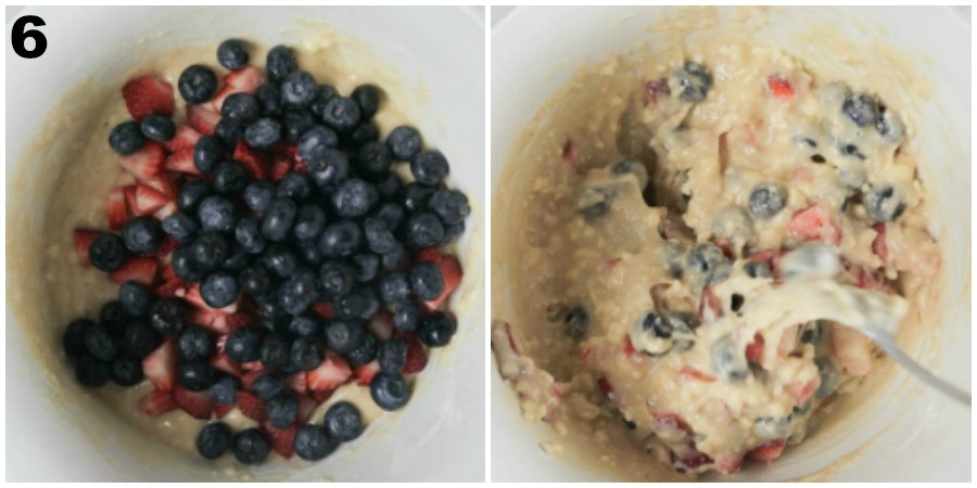 Adding blueberries and strawberries to cake batter in a white mixing bowl