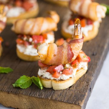 Creamy Bacon Shrimp Bruschetta recipe - Perfect appetizers for entertaining! This Creamy Bacon Shrimp Bruschetta recipe has it all with toasted baguette, a creamy garlic herb and bacon spread, balsamic vinaigrette, and THE BEST fresh basil and tomato bruschetta. Topped with a succulent bacon-wrapped shrimp! Make it for all your summer parties!