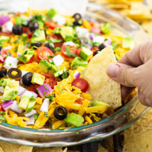 Easy layered taco dip in a round glass dish with a tortilla chip dipping into it