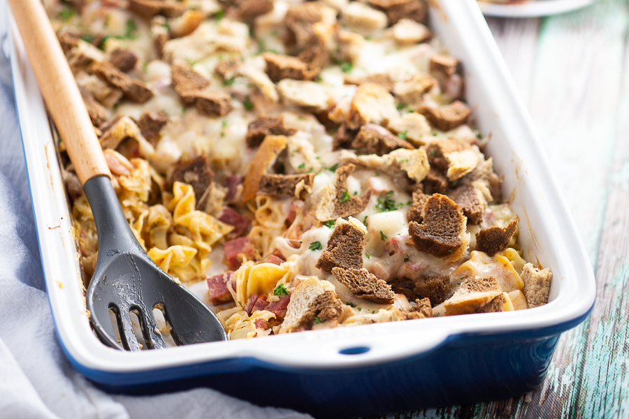 Reuben casserole in ceramic casserole dish on a green rustic wood background