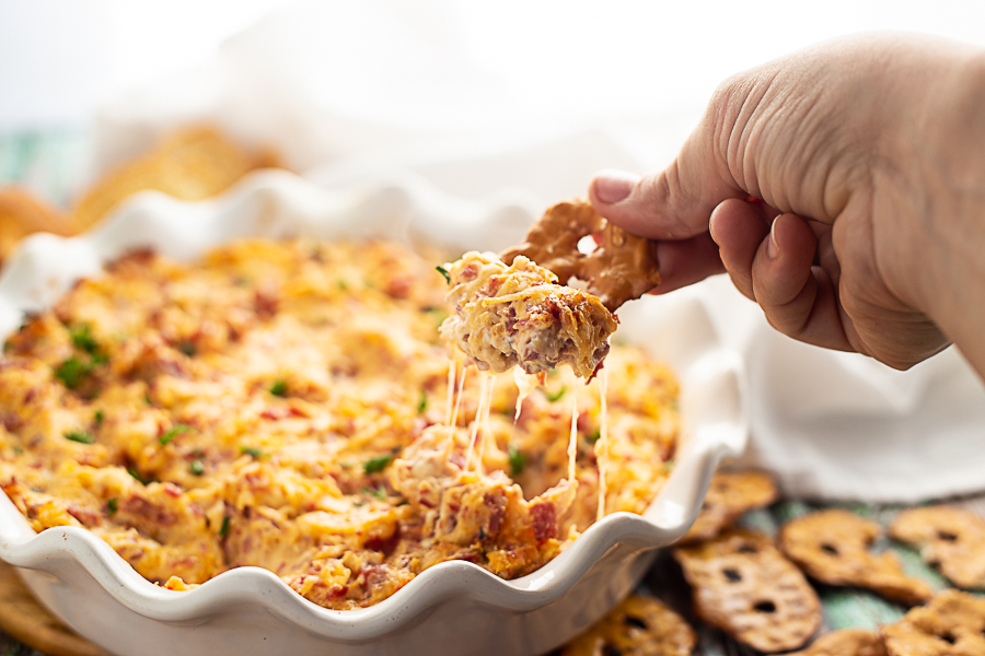 Reuben dip in a white ruffled pie dish with a pretzel chip being dipped in