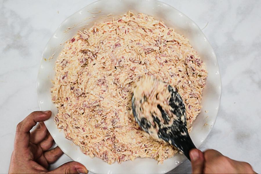 Reuben dip in white ruffled pie dish on white marble background