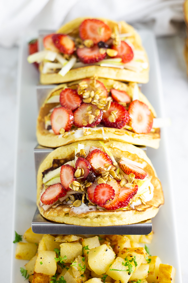 Pancake parfait tacos in a metal taco stand on a rectangle white plate with seasoned breakfast potatoes