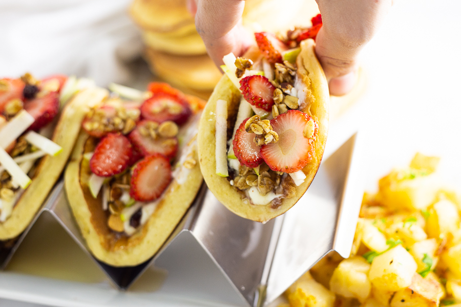 Hand picking up a pancake parfait taco from a taco holder on a white plate