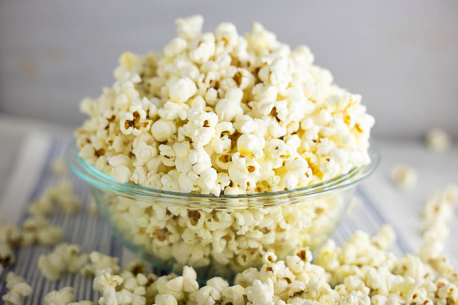 Popcorn in a clear class bowl on a white and blue striped placemat