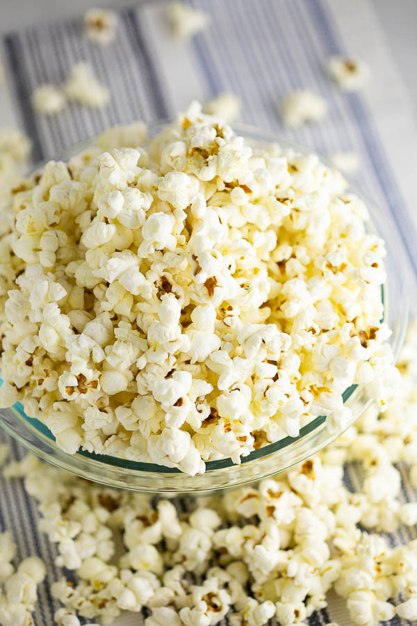 Popcorn in a glass bowl on a blue and white striped placemant