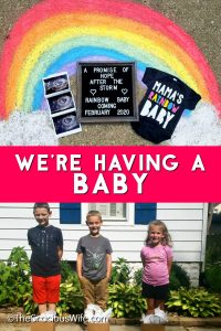 Rainbow drawn in chalk on a sidewalk with an ultrasound, a sign, and a onesie