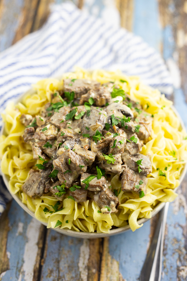Slow cooker beef stroganoff over egg noodles topped with parsley in a white bowl on a blue distressed wood background and a white and blue striped linen
