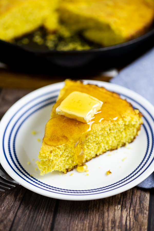 Wedge of cornbread topped with a pat of butter and honey on a white and blue plate on a rustic wood background
