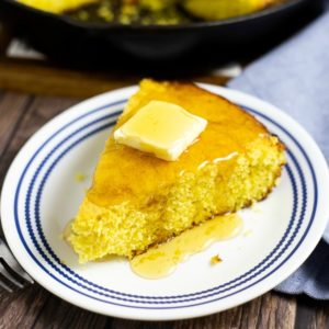Wedge of cornbread with butter and honey on a white and blue plate on a rustic wood background.
