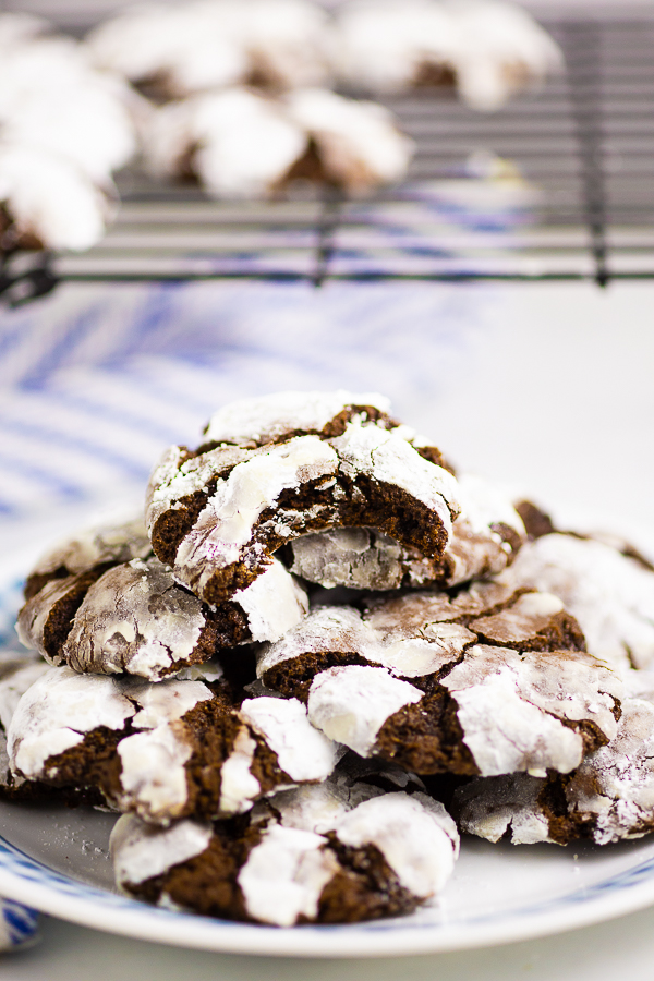 Chocolate crinkle cookies on a white plate with a cooling rack in the background