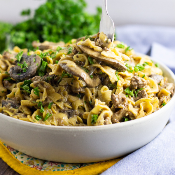 Juicy ground beef and warm noodles tossed in a creamy sauce seasoned with fresh mushrooms, onion, and garlic makes a classic easy comfort dish. Make this Ground Beef Stroganoff recipe in just one pot! This is THE BEST homemade, from scratch stroganoff you will ever make!