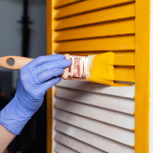 Hand with latex glove painting a door yellow with a paint brush