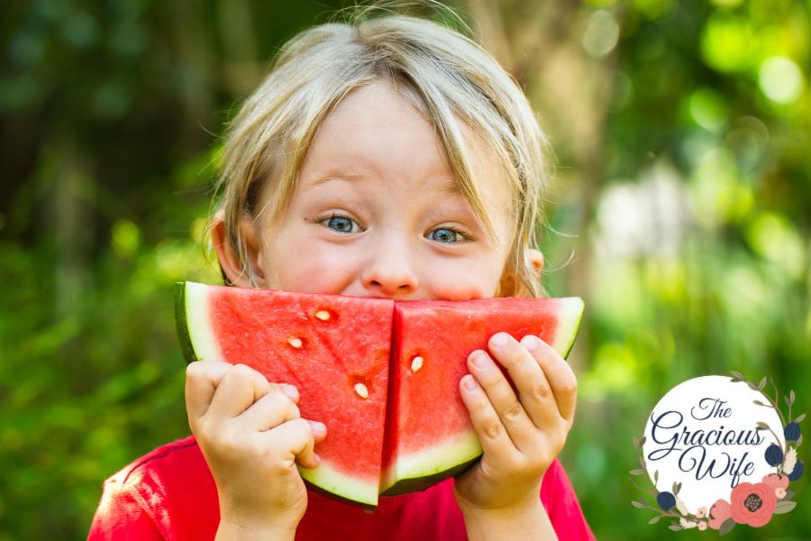 A little boy holding 2 wedges of watermelon in front of his face