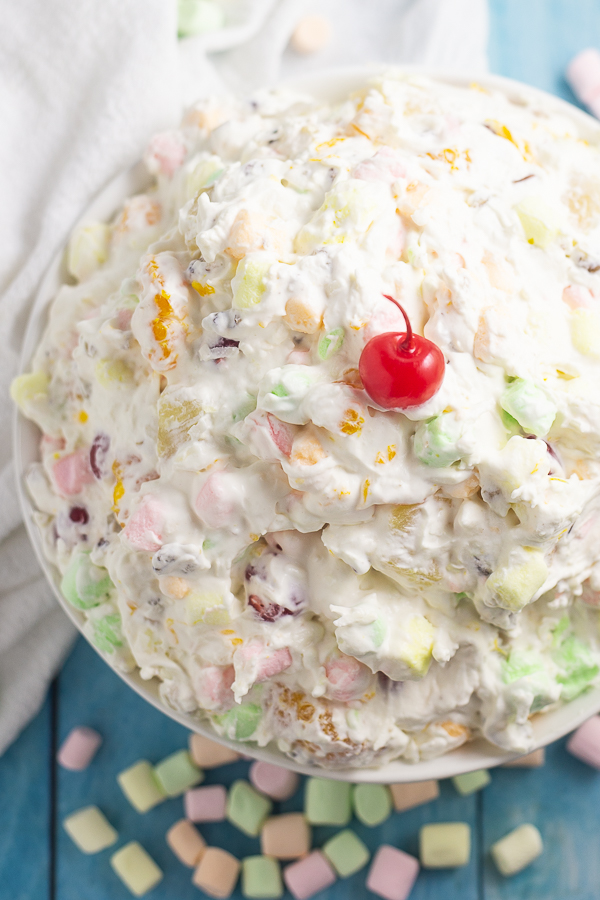 Overhead picture of a big bowl of ambrosia salad with a maraschino cherry on top. The bowl is surrounded by mini marshmallows and next to a white linen