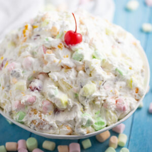 A big bowl of Ambrosia salad with a cherry on top with mini marshmallows scattered around it.