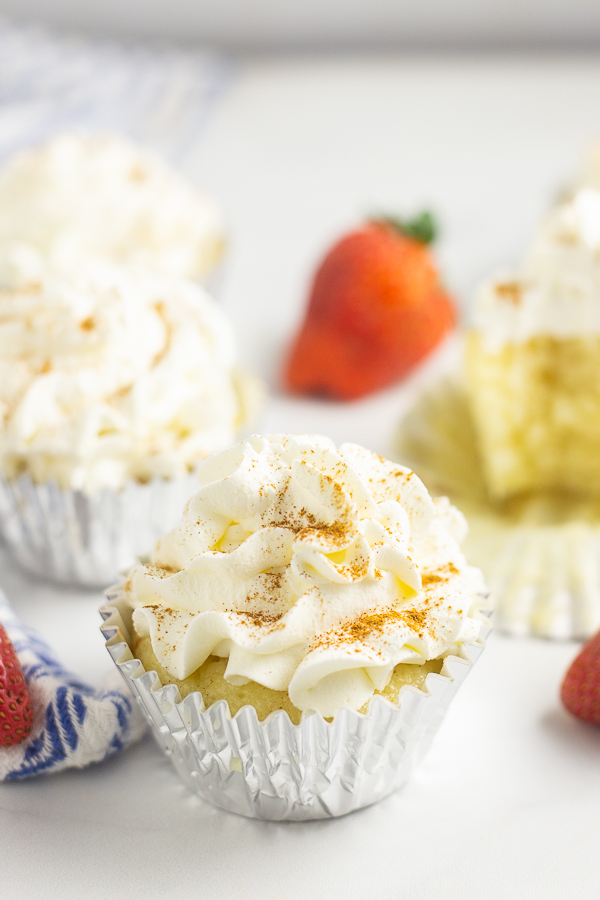 Tres Leches cupcake in a foil wrapper with a strawberry and more cupcakes in the background.