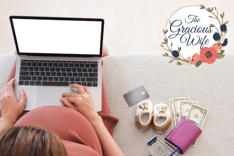 Pregnant mom sitting on a couch with a laptop on her lap next to baby shoes, wallet, credit card, and some cash
