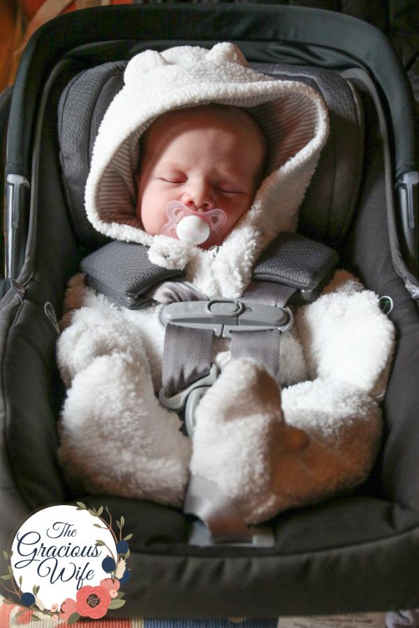 Newborn baby wearing a fuzzy bear bunting in a car seat