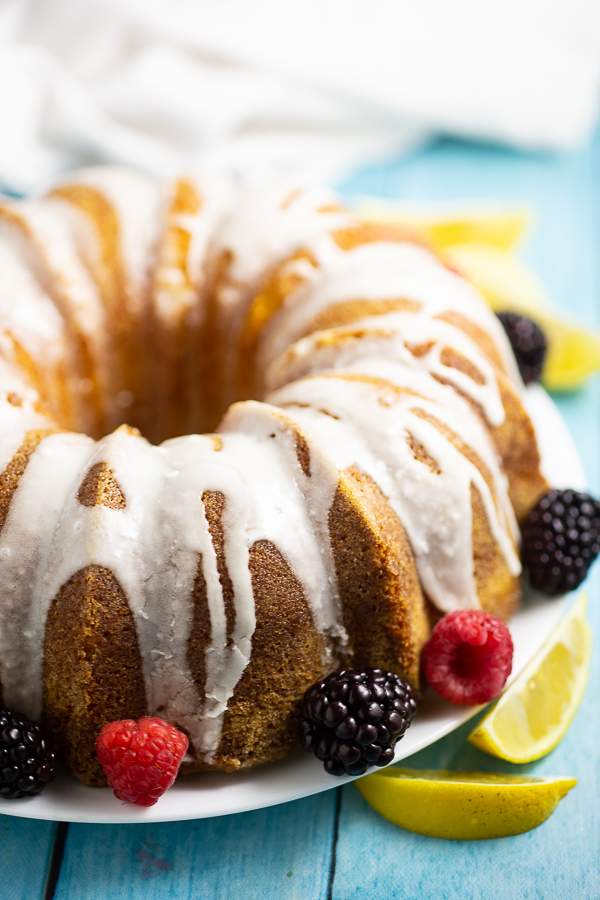 Side view of a Lemon buttermilk pound cake with lemon glaze with a linen behind it. The cake is surrounded by fresh raspberries and blackberries and lemon wedges.
