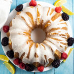 Overhead picture of a lemon buttermilk pound cake with lemon glaze drizzled on top next to fresh blackberries and raspberries and lemon wedges